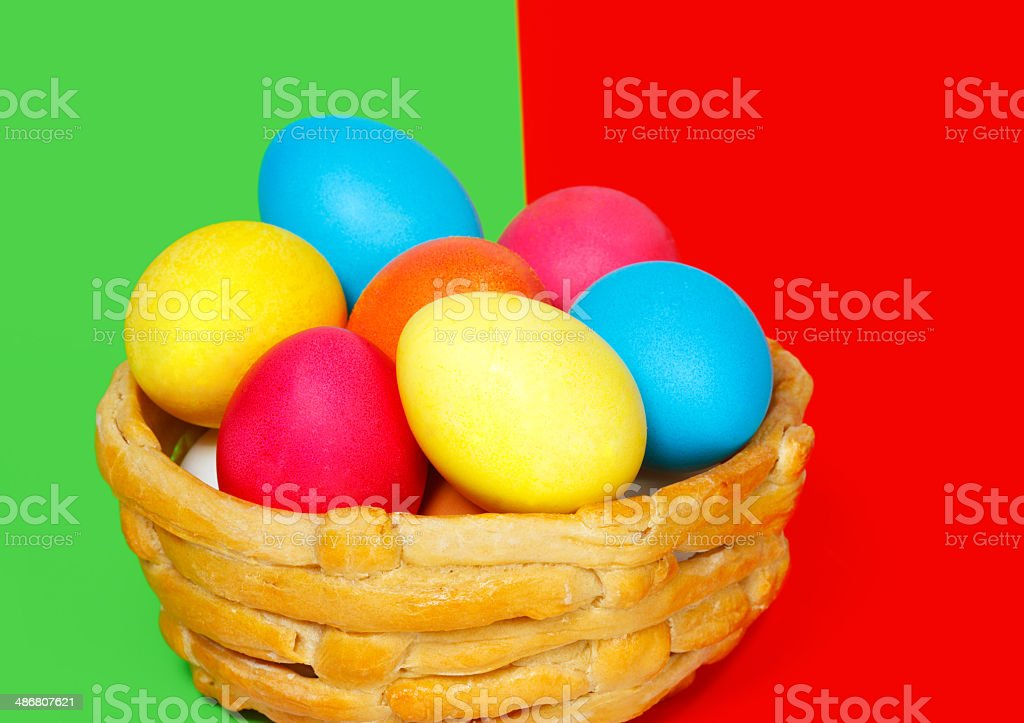 Baked basket with Easter colored eggs on the color background royalty-free stock photo