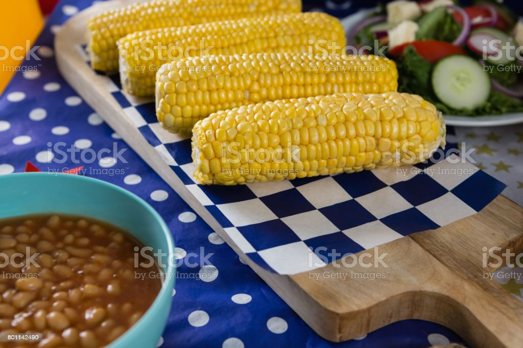 Baked beans and corn cob on wooden table with 4th july theme stock photo