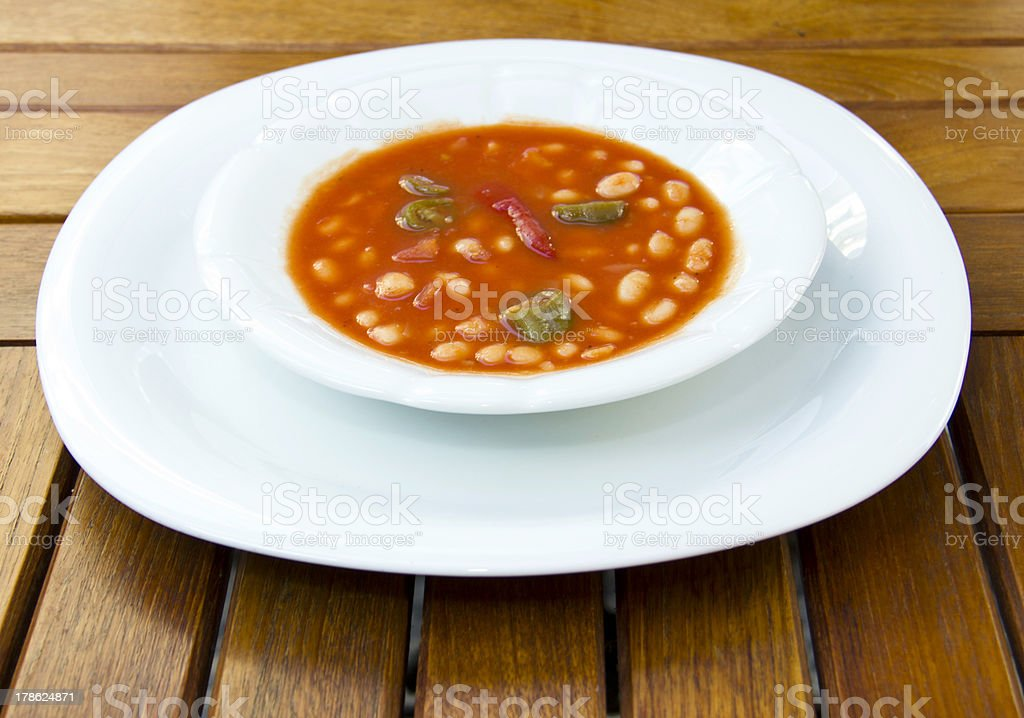 Baked beans and sausage in a white bowl royalty-free stock photo