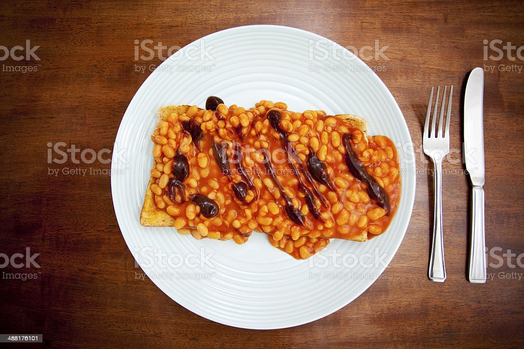 Baked beans on toast with brown sauce stock photo