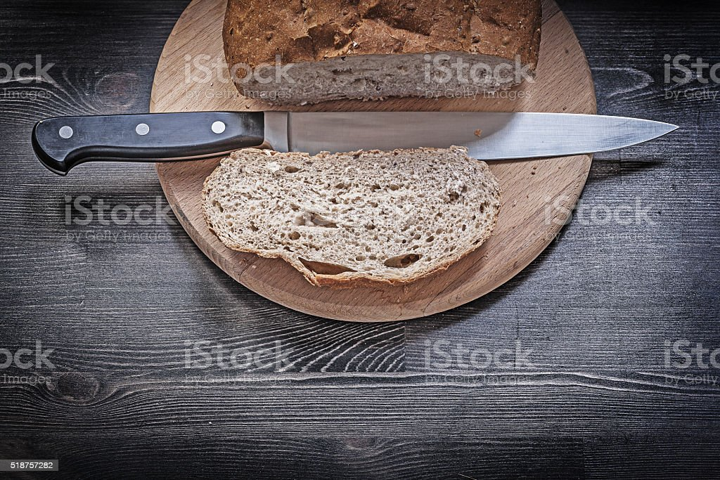 Baked brown bread wooden chopping board carving knife stock photo