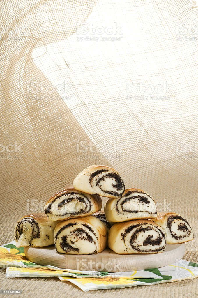 Baked bun with poppy seeds on a wood board. royalty-free stock photo