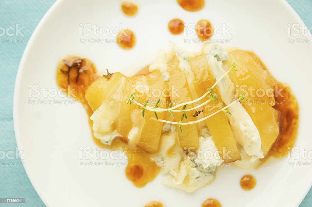 Baked Caramelized pear with cheese gorgonzola and thyme on blue stock photo