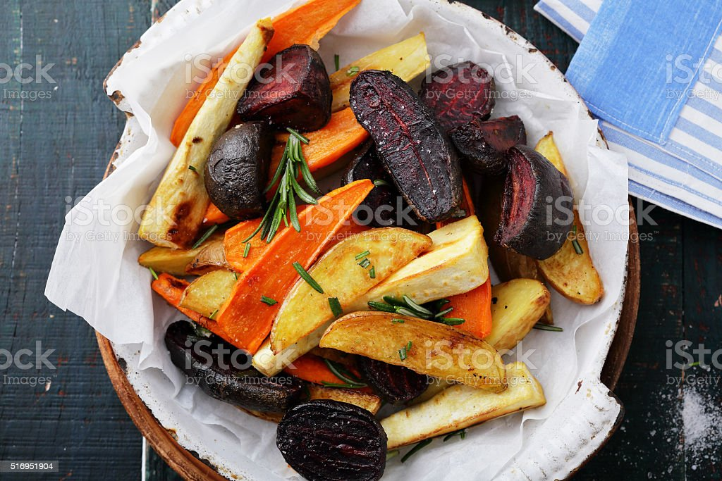 baked carrots and beets with herbs stock photo