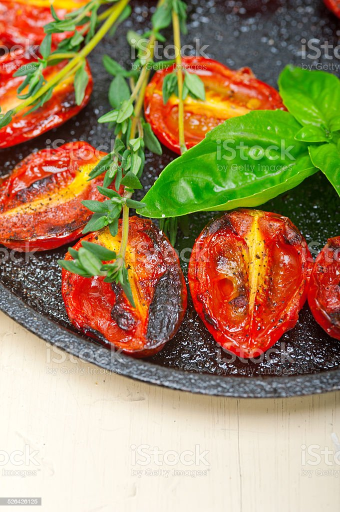 baked cherry tomatoes with basil and thyme stock photo