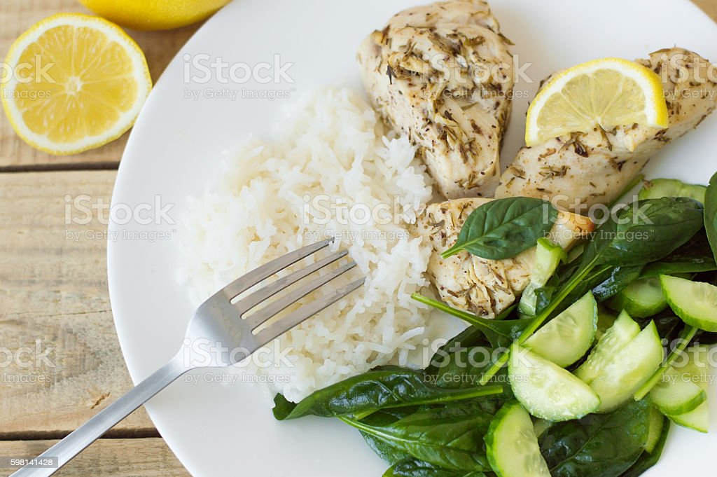 Baked chichen breasts with lemon, white rice and green spinach stock photo