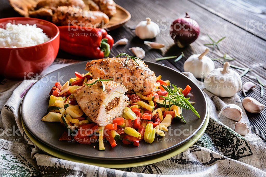 Baked chicken breast stuffed with cheese, tomato and basil stock photo