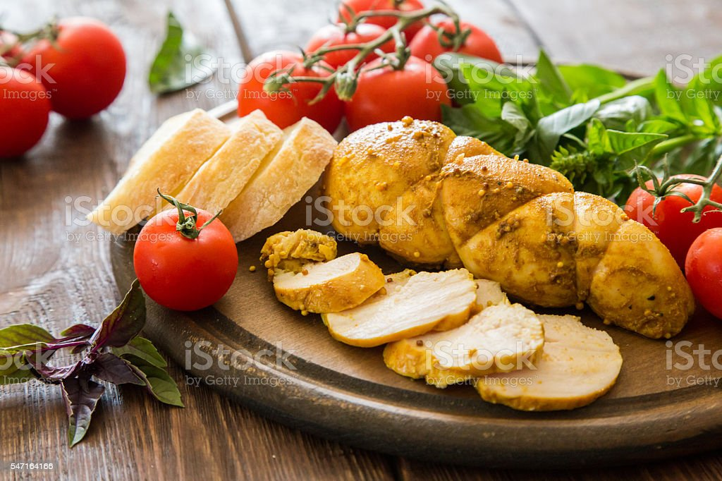Baked chicken breast (Pastrami) with spices, tomato and basil. stock photo