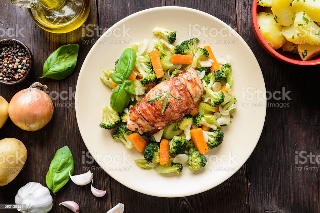 Baked chicken breast wrapped in bacon with boiled potatoes stock photo