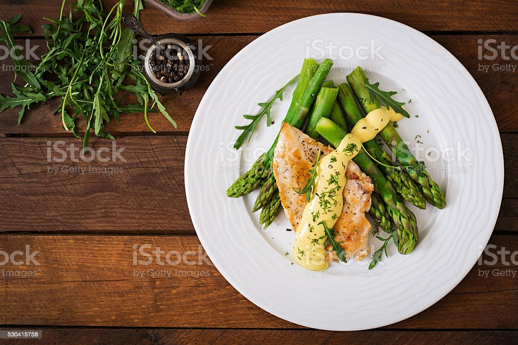 Baked chicken garnished with asparagus and herbs stock photo