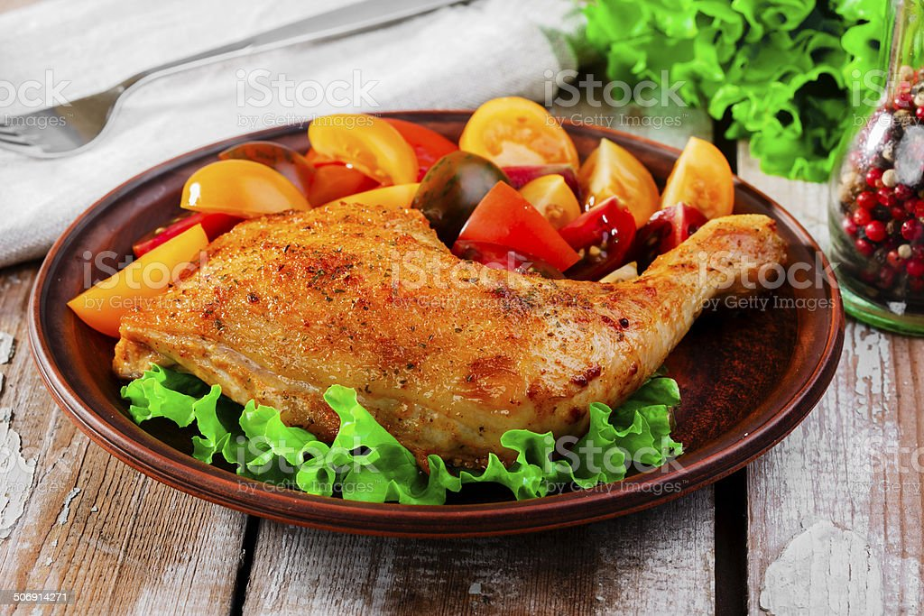 baked chicken leg with tomatoes stock photo