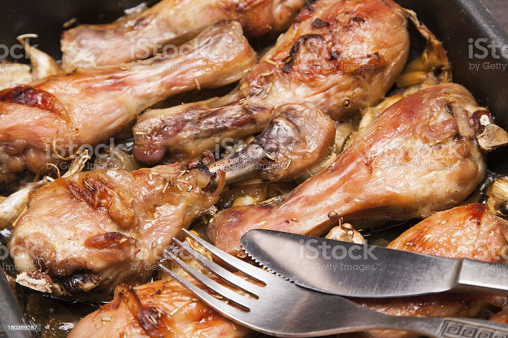 baked chicken legs in tray on black wooden royalty-free stock photo