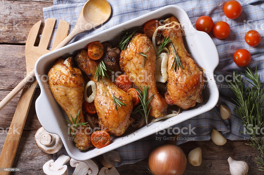 Baked chicken legs with vegetables close-up horizontal top view stock photo