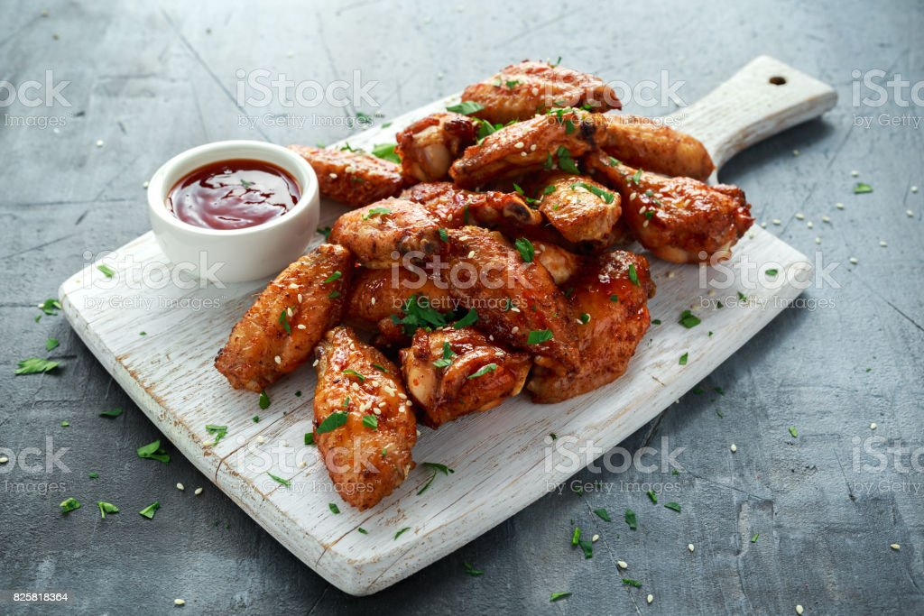 Baked chicken wings with sesame seeds and sweet chili sauce on white wooden board. stock photo