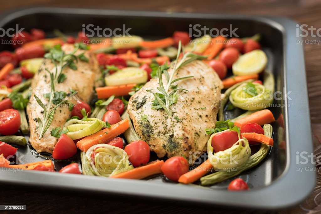 Baked chicken with basil, carrot and cherry tomatoes stock photo