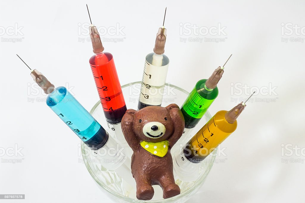 baked  clay teddy bear with plastic syringes containing multicolor solutions stock photo