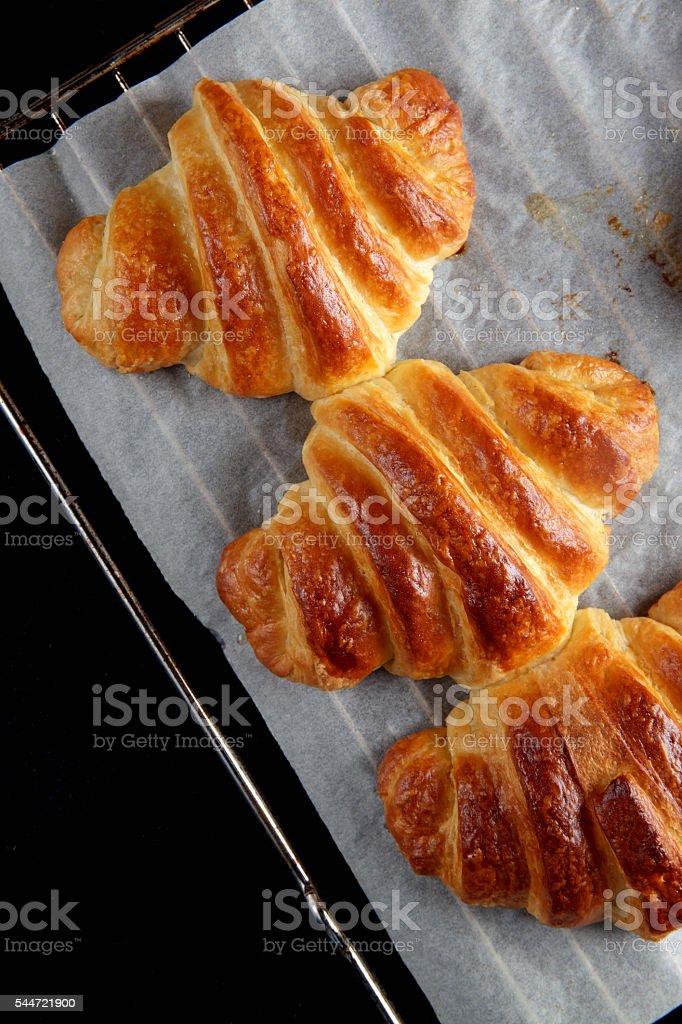 baked croissants on a baking sheet. Healthy breakfast comfort stock photo