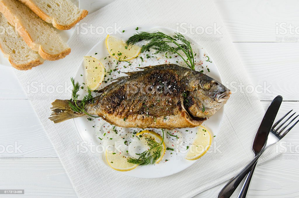 baked dorado on plate on  white background with lemon dill stock photo