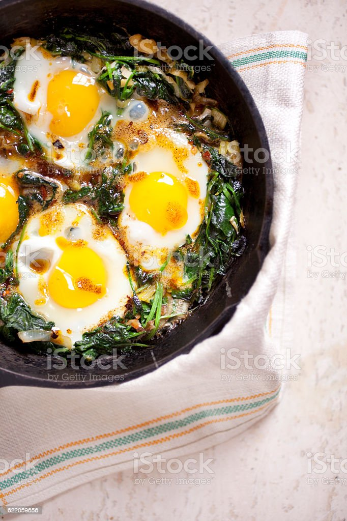 Baked Eggs with Kale and Spiced Brown Butter stock photo