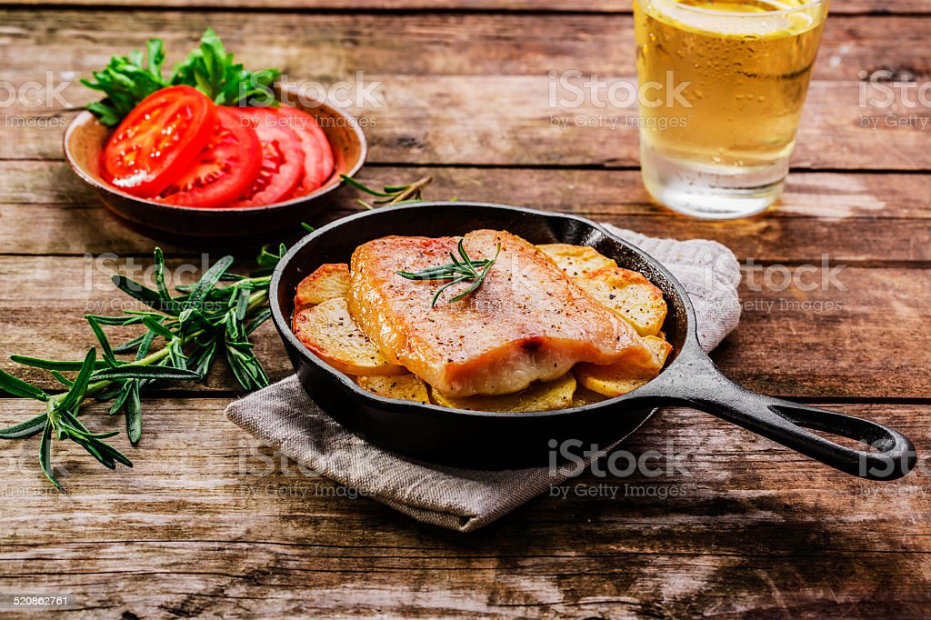Baked fish fillets with potatoes in a frying pan stock photo