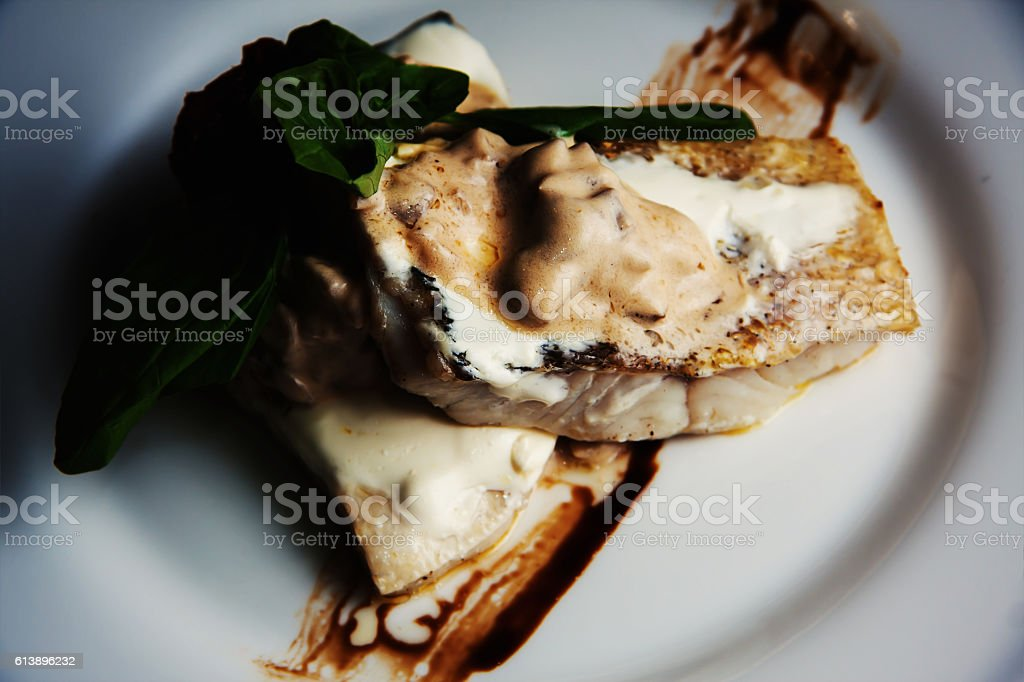 baked fish in cream sauce stock photo