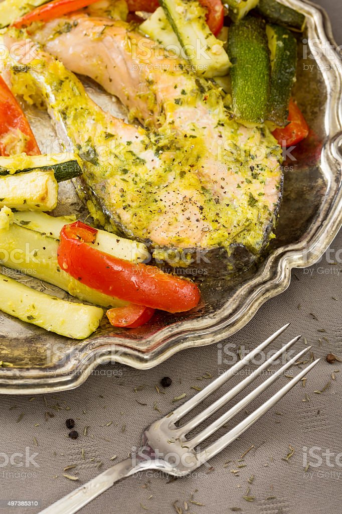 baked fish on a plate with garnish stock photo