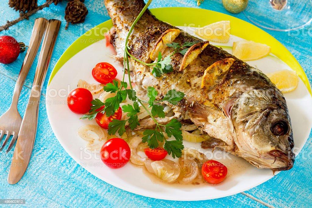 Baked fish (carp) with onion and lemon stock photo