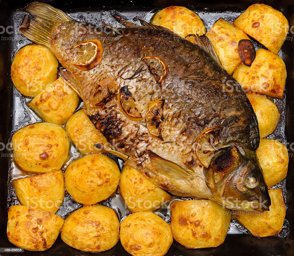 Baked fish with potatoes stock photo