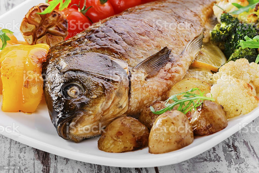 baked fish with vegetables stock photo