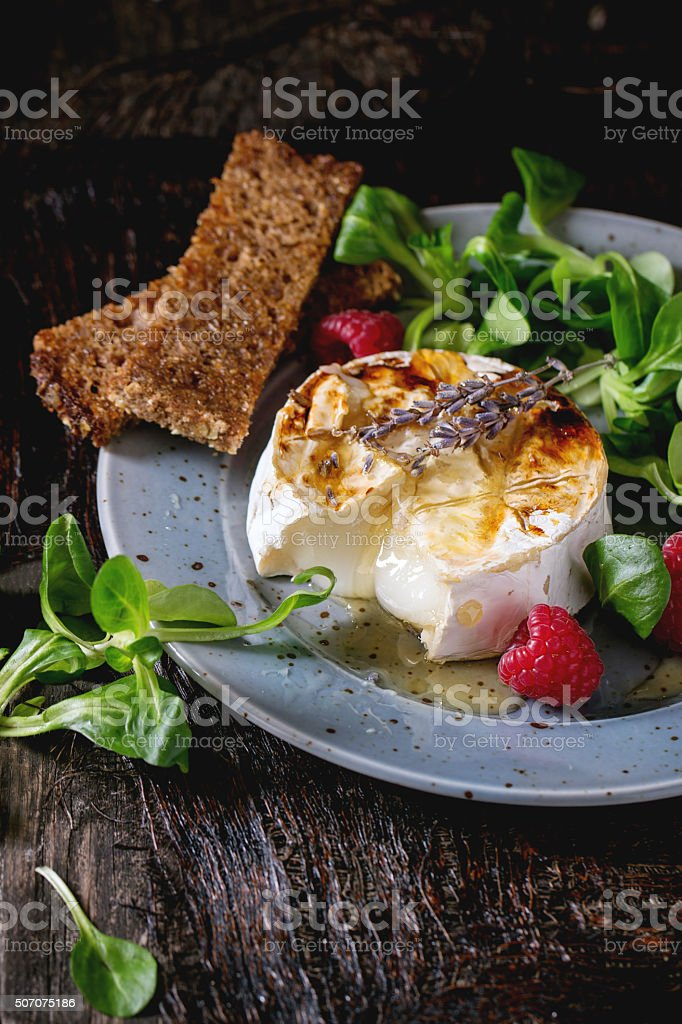 Baked Goat cheese with honey and raspberries stock photo