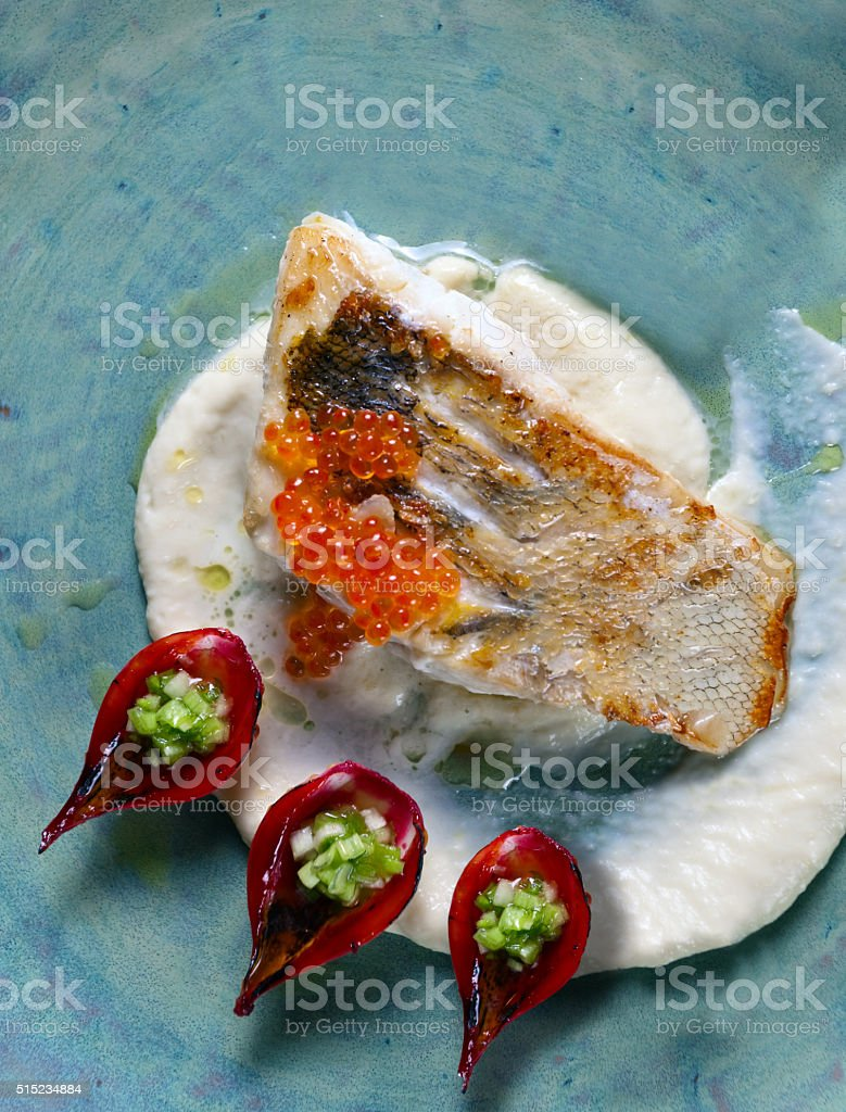 baked halibut with red caviar stock photo