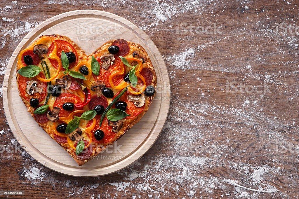 Baked heart-shaped homemade pizza stock photo