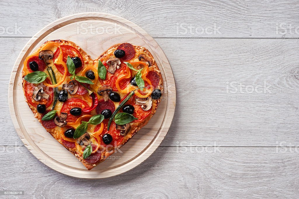 Baked heart-shaped homemade pizza stock photo
