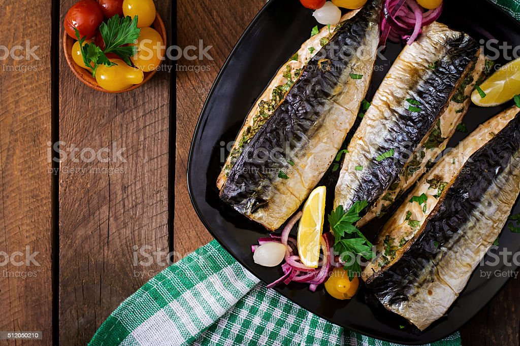 Baked mackerel with herbs and garnished with lemon stock photo