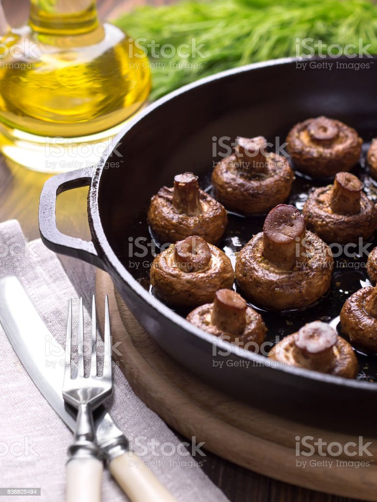 Baked mushrooms in a pan on the dark wooden table. stock photo