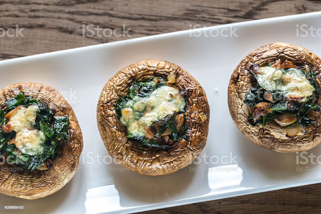 Baked mushrooms stuffed with spinach and cheese stock photo