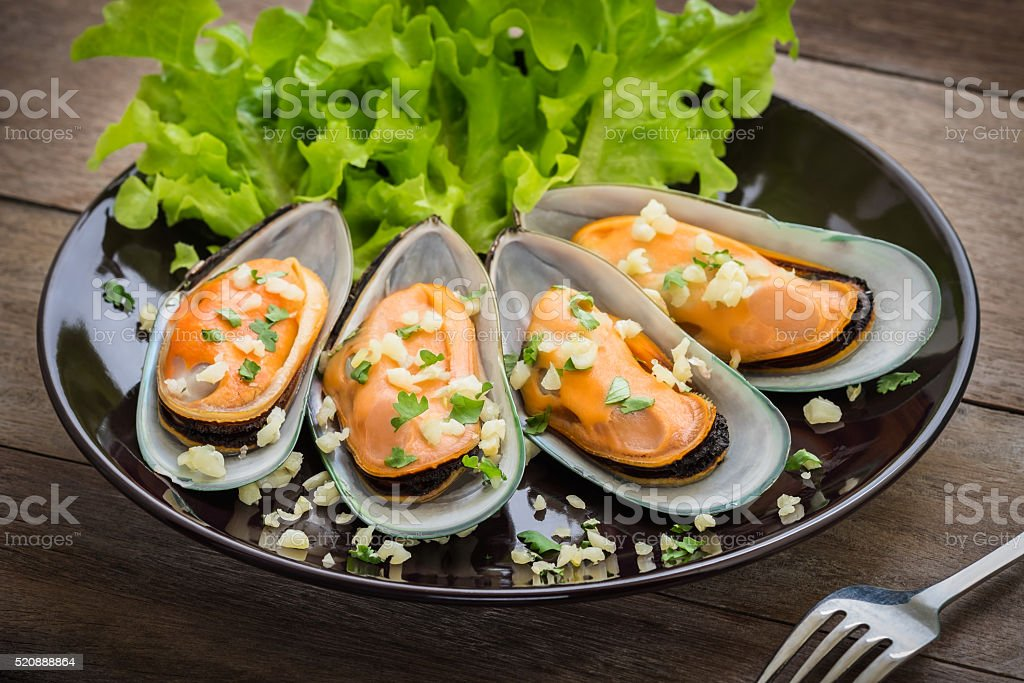 Baked mussels with garlic on plate stock photo
