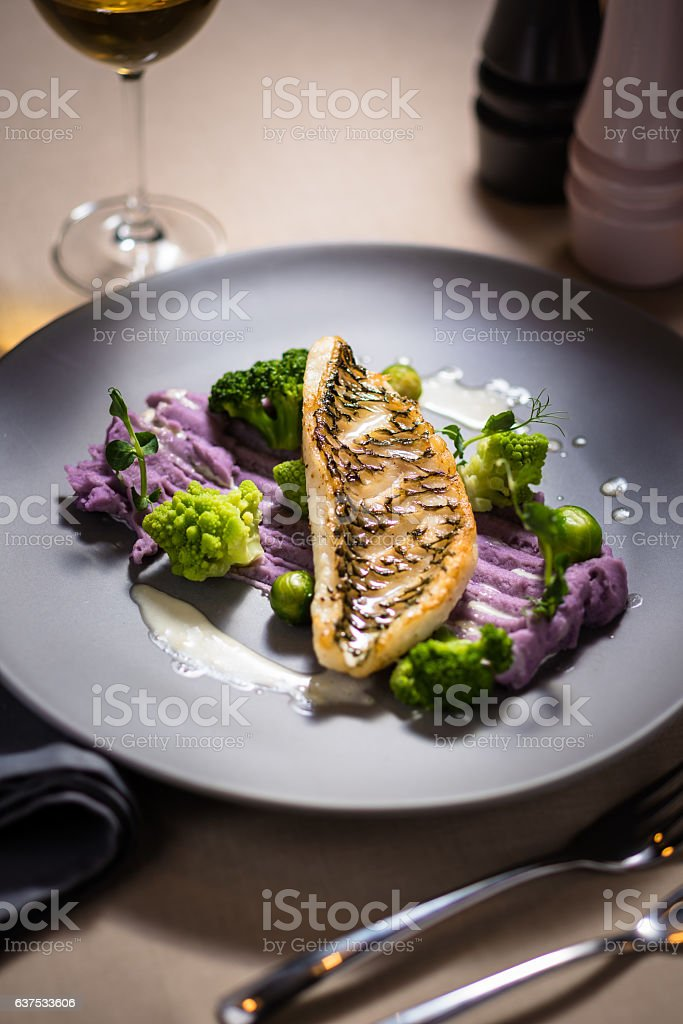 Baked parrotfish fillet served with Vitelotte potatoes stock photo