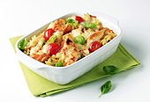 Baked pasta dish adorned with red tomatoes and veggies