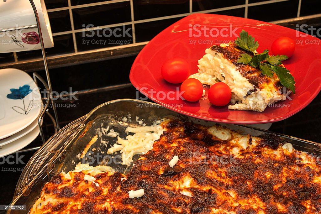Baked pasta portion in red plate stock photo