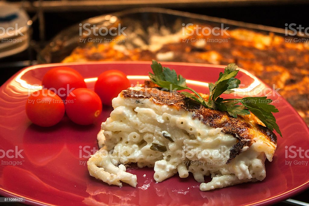 Baked pasta service in red plate stock photo