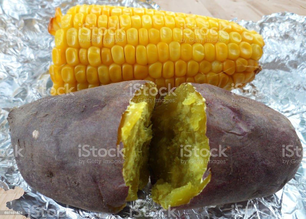 Baked potato and corn on aluminum foil stock photo