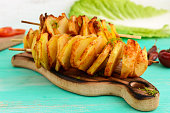 Baked potato circles on a bamboo skewer