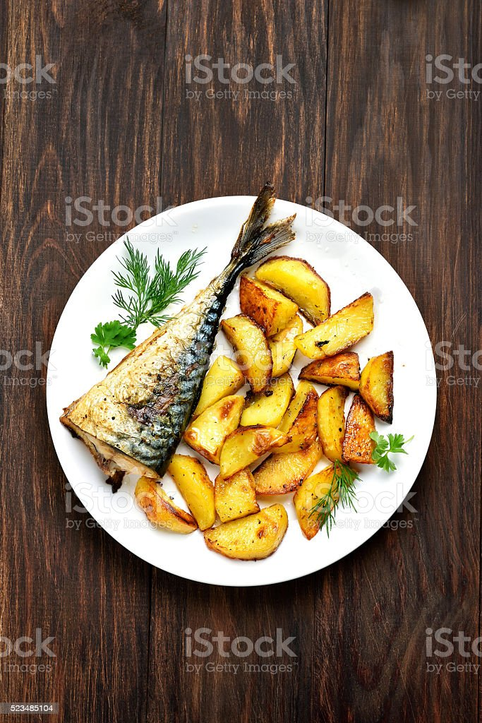 Baked potato wedges and mackerel fish stock photo