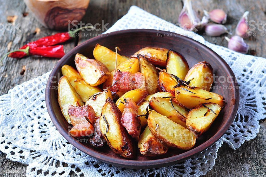 Baked potato with bacon, rosemary, olive oil and sea salt stock photo