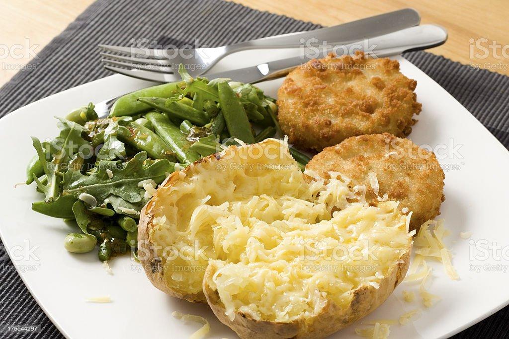 Baked potato with fishcakes and salad royalty-free stock photo
