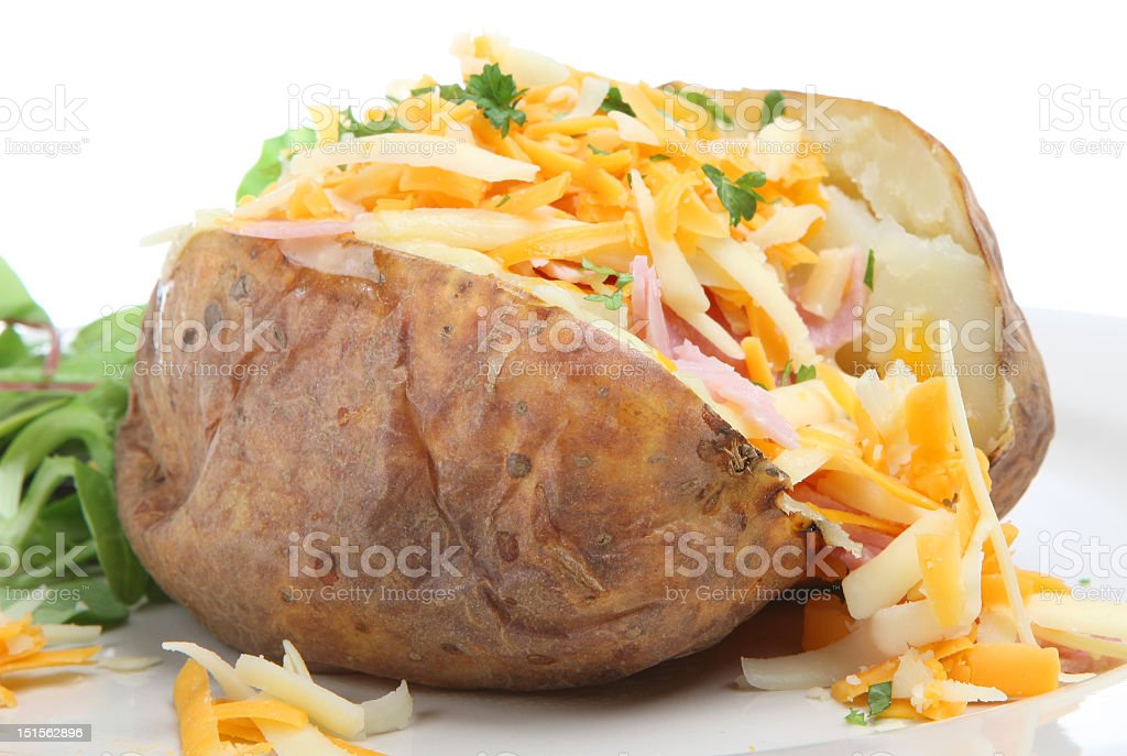 Baked potato with ham, cheese, and parsley  stock photo
