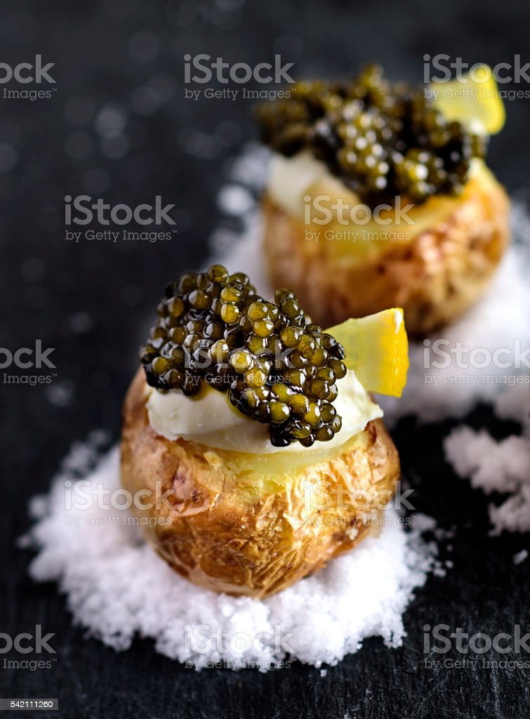 Baked Potatoes with Black Caviar stock photo