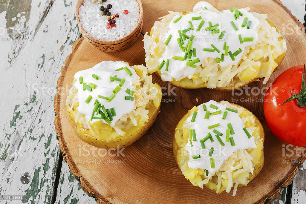 Baked potatoes with cheese and toppings stock photo