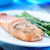 Baked salmon and asparagus on a white plate
